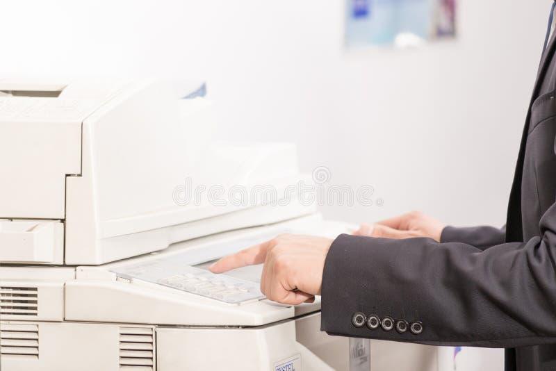 Homem que usa uma máquina da cópia (DOF raso) imagem de stock