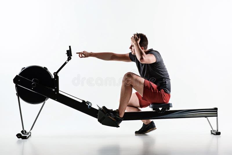 Homem que usa uma máquina da imprensa em um clube de aptidão fotos de stock