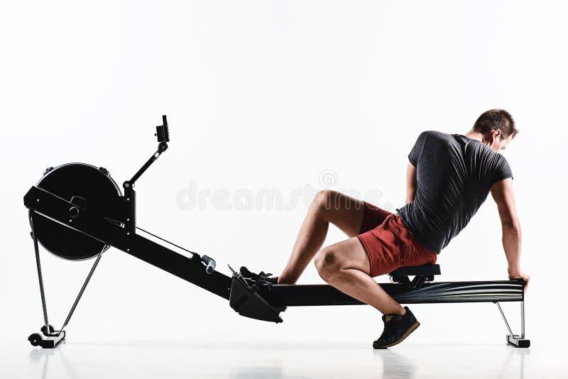 Homem que usa uma máquina da imprensa em um clube de aptidão imagens de stock royalty free