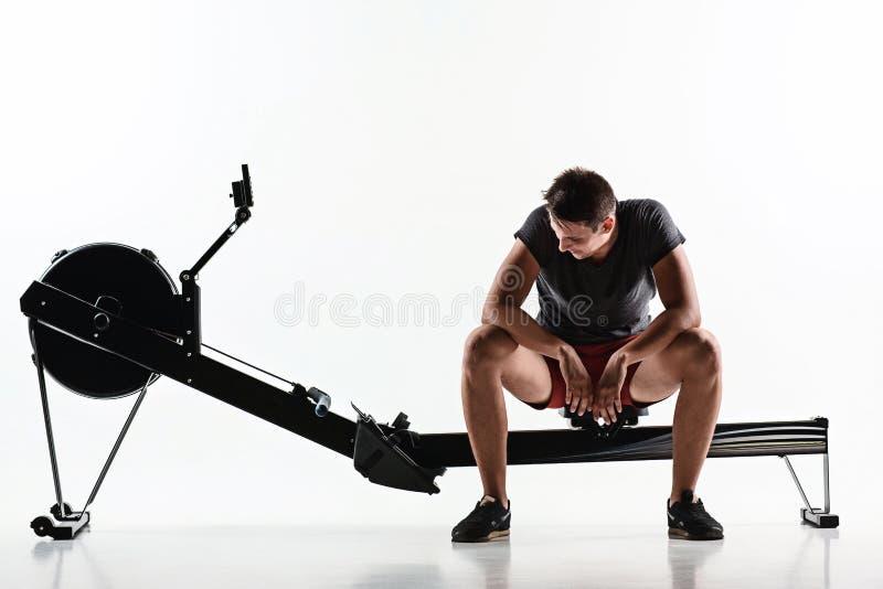 Homem que usa uma máquina da imprensa em um clube de aptidão foto de stock