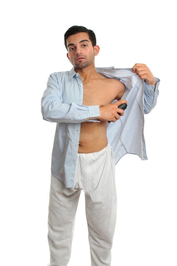 Homem que usa underarm o pulverizador perspirant do desodorizante imagem de stock