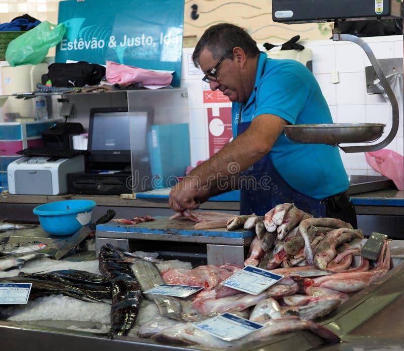 Homem que vende peixes no mercado em Faro Portugal imagens de stock