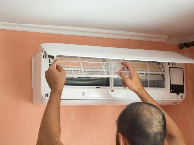 Homem que verifica o filtro do condicionador de ar imagens de stock