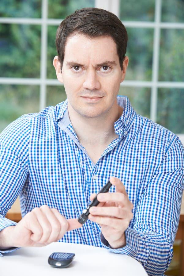 Homem que verifica o sangue Sugar Level At Home fotografia de stock
