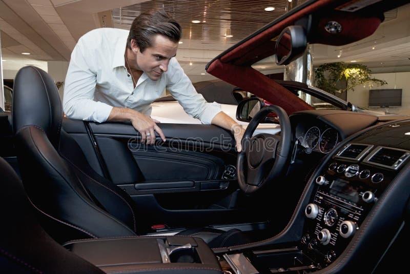 Homem que verifica para fora seu carro novo foto de stock royalty free