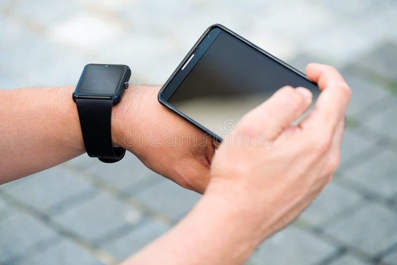 Homem que verifica seu smartwatch fora imagens de stock royalty free