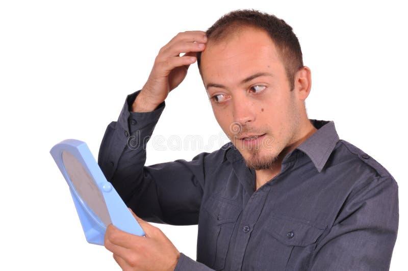 Homem que verifica sua queda de cabelo no espelho imagens de stock