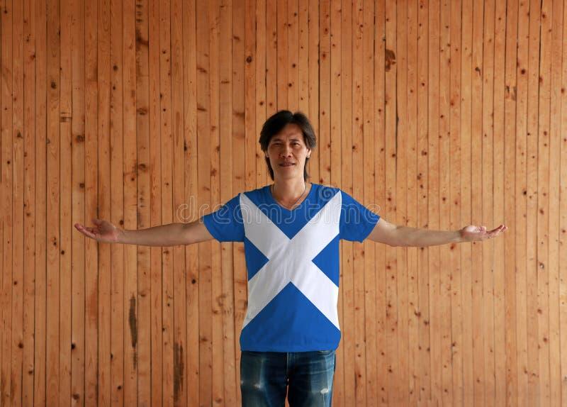 Homem que veste a camisa da cor da bandeira de Escócia e que está com os braços largamente abertos no fundo de madeira da parede imagem de stock royalty free