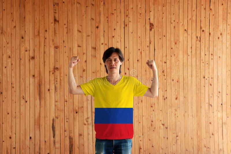 Homem que veste a cor da bandeira de Colômbia da camisa e que está com o punho aumentado no fundo de madeira da parede foto de stock