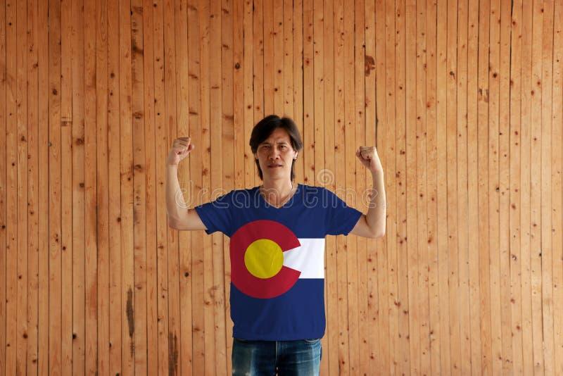 Homem que veste a cor da bandeira de Colorado da camisa e que está com o punho aumentado no fundo de madeira da parede imagem de stock