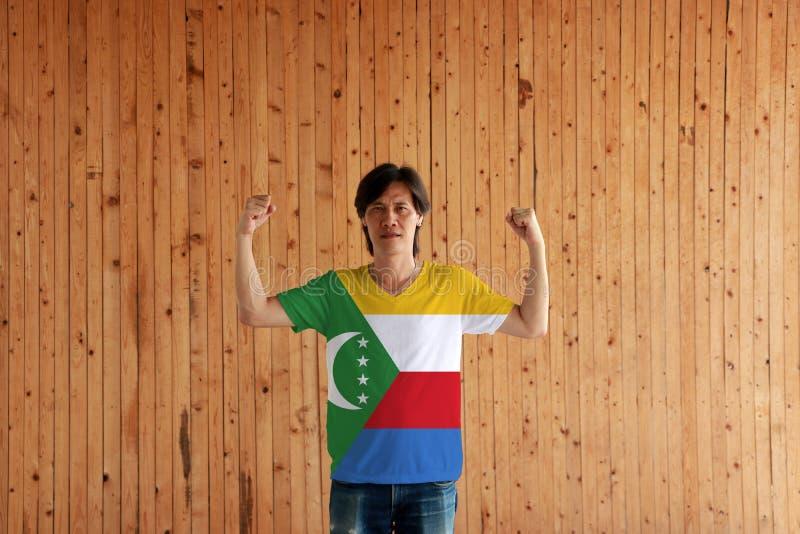 Homem que veste a cor da bandeira de Comores da camisa e que está com o punho aumentado no fundo de madeira da parede imagens de stock