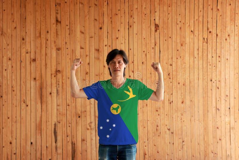 Homem que veste a cor da bandeira de Ilhas Christmas da camisa e que está com o punho aumentado no fundo de madeira da parede imagens de stock royalty free