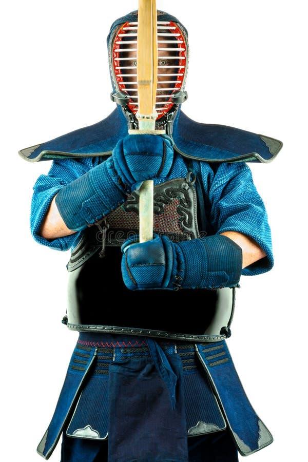 Homem que vestem uma armadura do kendo com capacete e luvas que guardam uma espada de bambu foto de stock royalty free