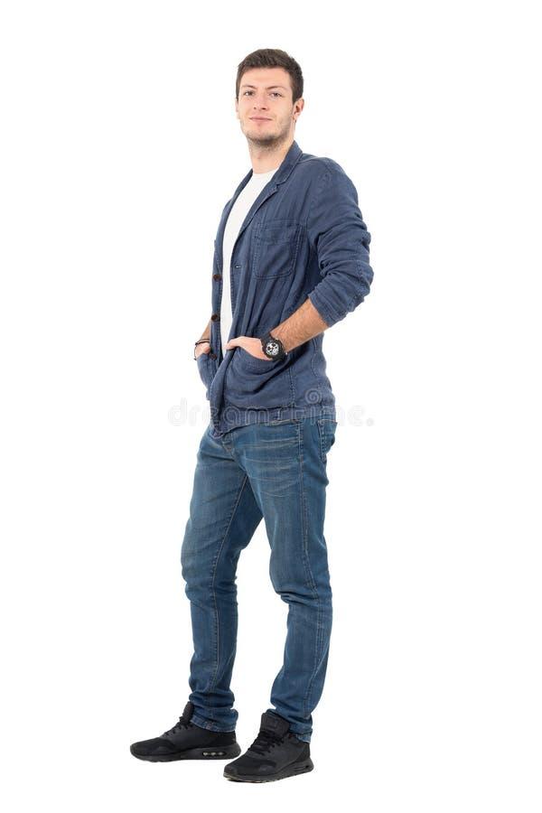 Homem relaxado de sorriso nas calças de brim e na camisa da sarja de Nimes com mãos em uns bolsos imagem de stock royalty free