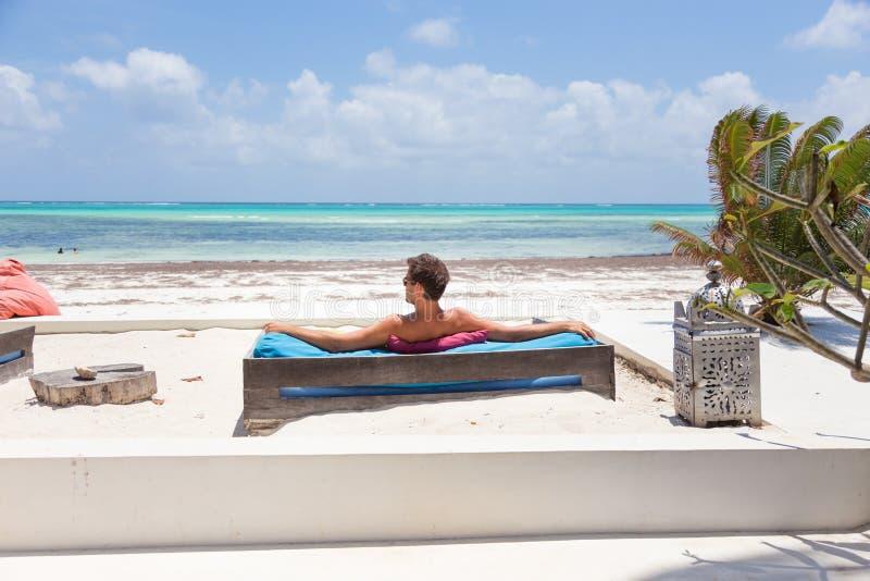 Homem relaxado no vadio luxuoso que aprecia férias de verão na praia bonita fotografia de stock royalty free