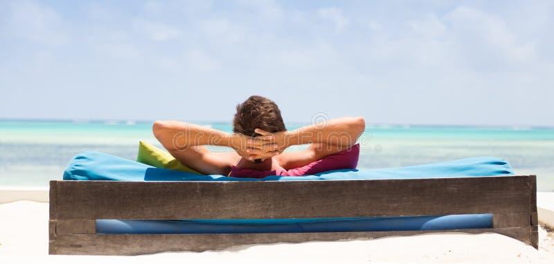 Homem relaxado no vadio luxuoso que aprecia férias de verão na praia bonita imagem de stock royalty free