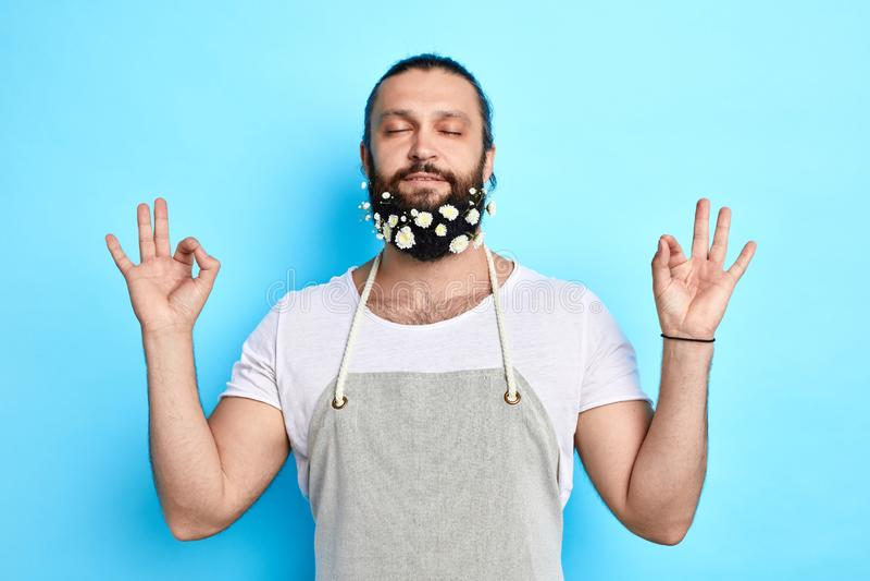 Homem relaxado novo com as flores em sua barba que medita, imagem de stock royalty free