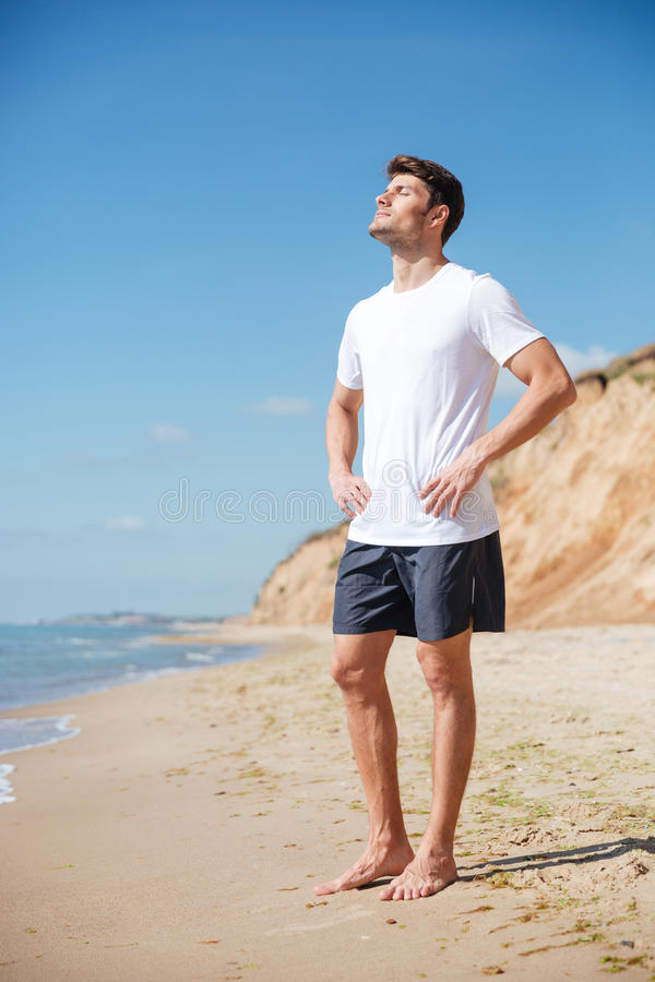 Homem relaxado que está com os pés descalços na praia fotos de stock