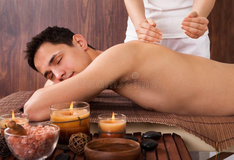Homem relaxado que recebe a massagem do ombro nos termas imagem de stock