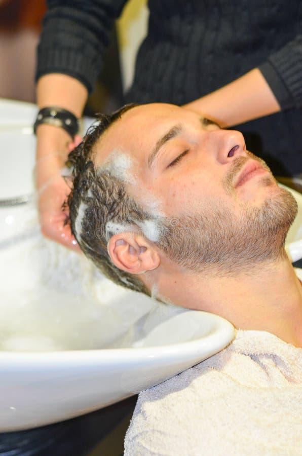 Homem relaxado shampooed por seu cabeleireiro fotos de stock royalty free