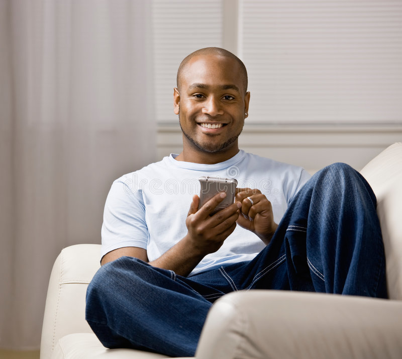 Homem Relaxed que usa o organizador eletrônico fotografia de stock royalty free
