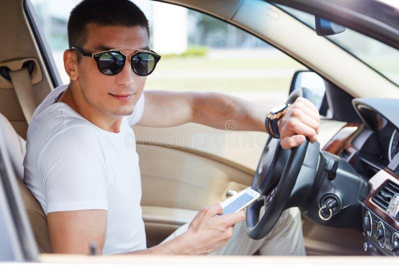 Homem rico novo seguro que ajusta seu telefone esperto e que olha a câmera ao sentar-se no carro imagem de stock royalty free