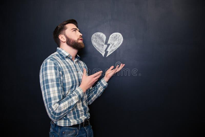 Homem romântico triste que guarda o coração quebrado tirado sobre o fundo do quadro-negro foto de stock