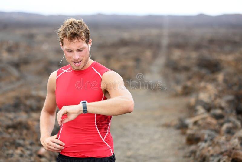 Homem running do atleta que olha o monitor da frequência cardíaca fotos de stock royalty free