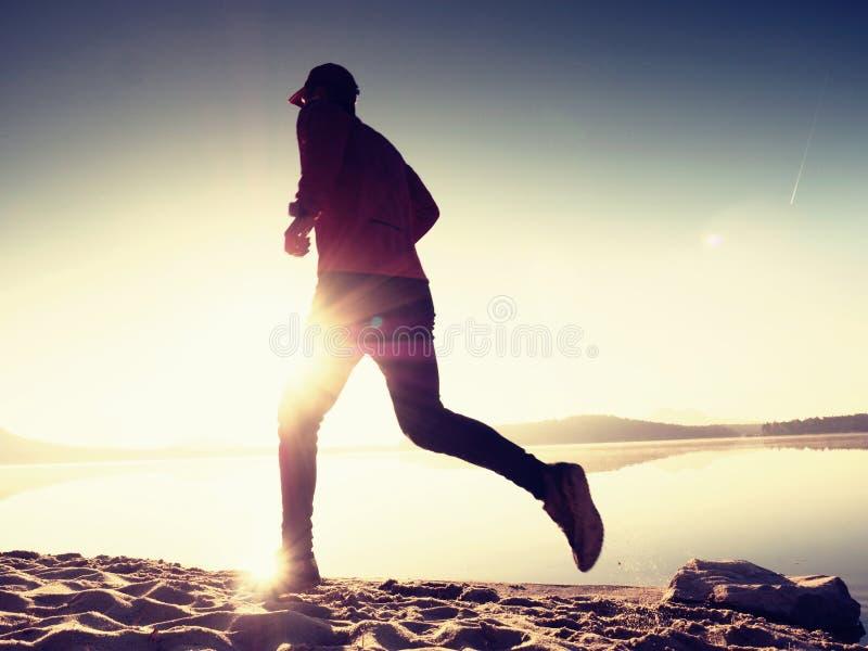 Homem running na praia Desportista corrido no boné de beisebol fotos de stock royalty free