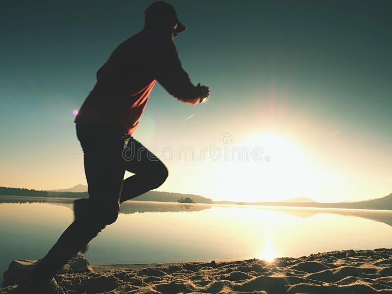 Homem running na praia Desportista corrido no boné de beisebol imagens de stock royalty free