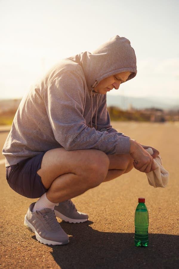 Homem running que descansa na estrada fotografia de stock