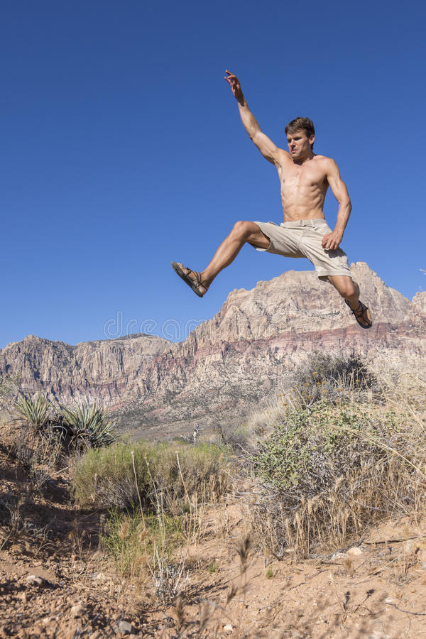 Homem running que salta altamente sobre arbustos no deserto foto de stock