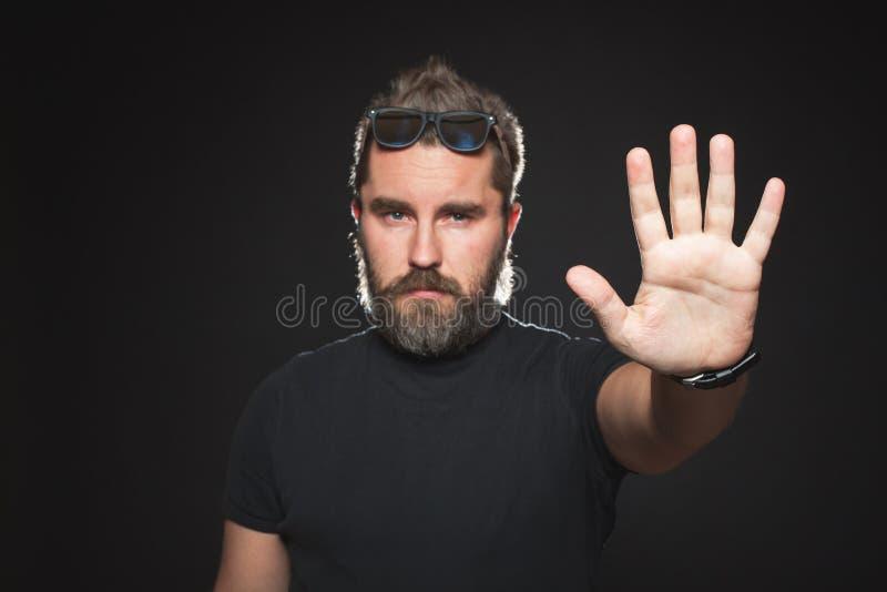 Homem sério com a barba em uma camisa preta e em óculos de sol em um fundo preto no estúdio Indivíduo seguro que está na frente d fotos de stock royalty free