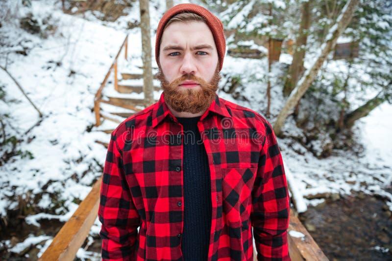 Homem sério com a barba na camisa de manta na floresta do inverno fotografia de stock
