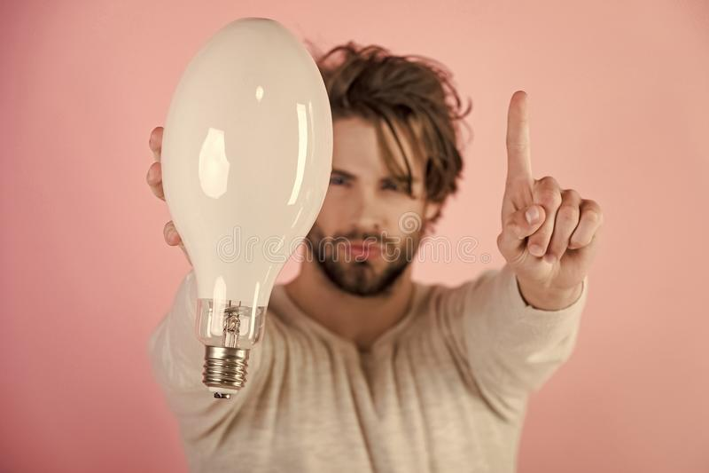 Homem sério com a lâmpada grande da posse bagunçado do cabelo, ideia, solução foto de stock