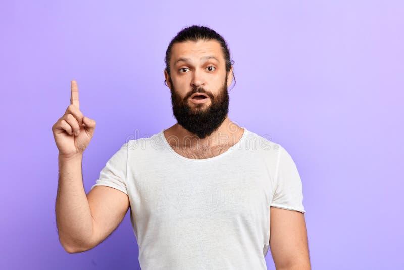 Homem sério com o dedo aumentado que olha a câmera imagem de stock