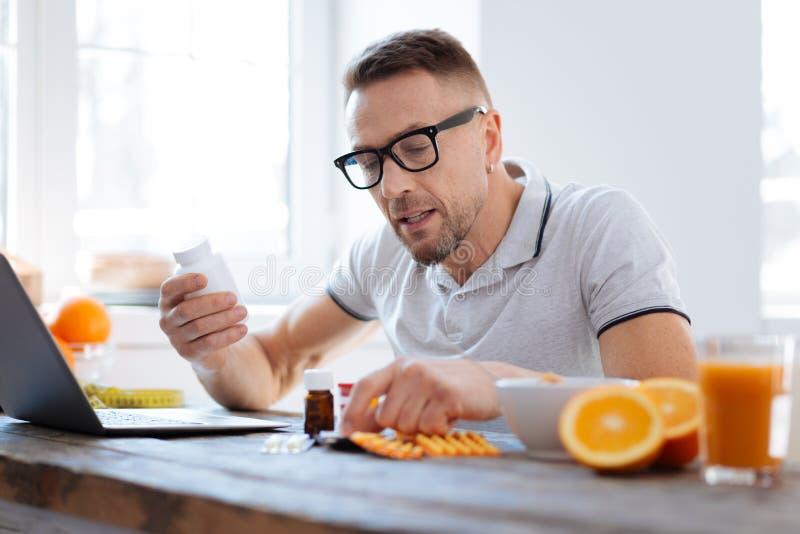 Homem sério concentrado que toma suplementos biohacking fotografia de stock