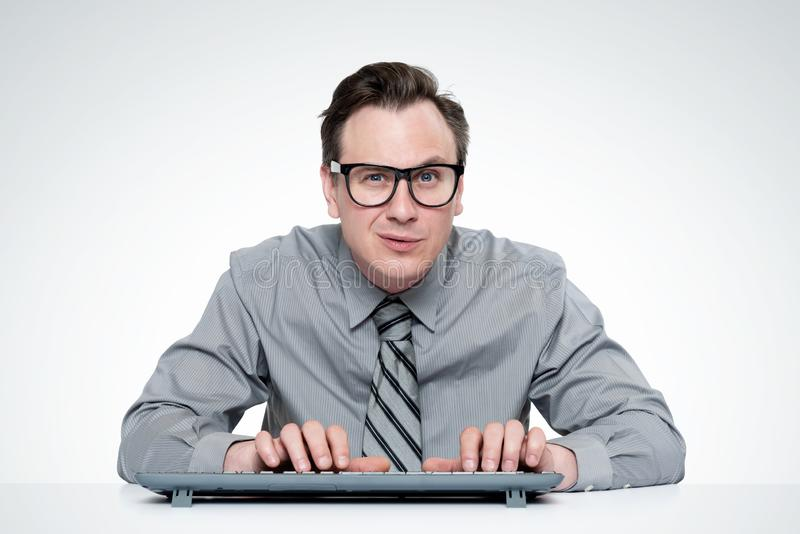 Homem sério em uma camisa e laço, vidros vestindo, trabalhando em um computador, em claro - fundo cinzento imagens de stock royalty free