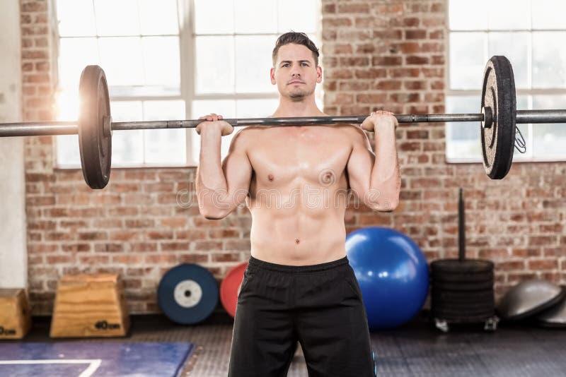 Homem sério muscular que faz o halterofilismo imagens de stock