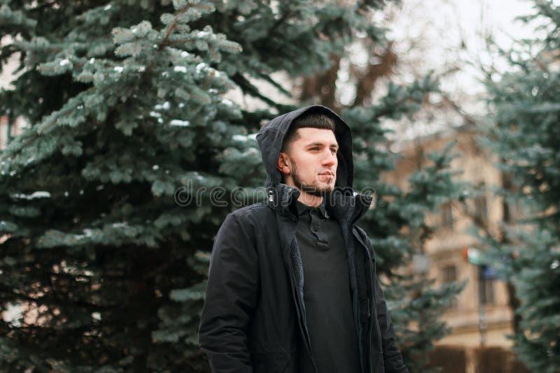 Homem sério novo que toma em sua capa no parque da cidade do inverno fotos de stock royalty free