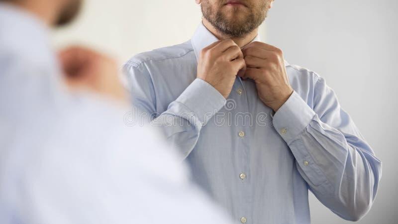 Homem sério que abotoa sua camisa no humor otimista, preparando-se para o trabalho fotos de stock