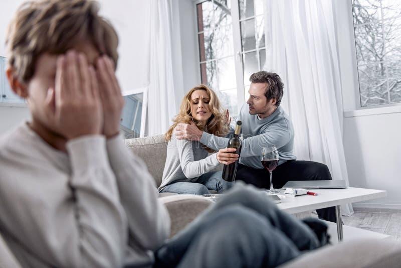 Homem sério que agita sua esposa alcoólica pelos ombros ao falar fotos de stock
