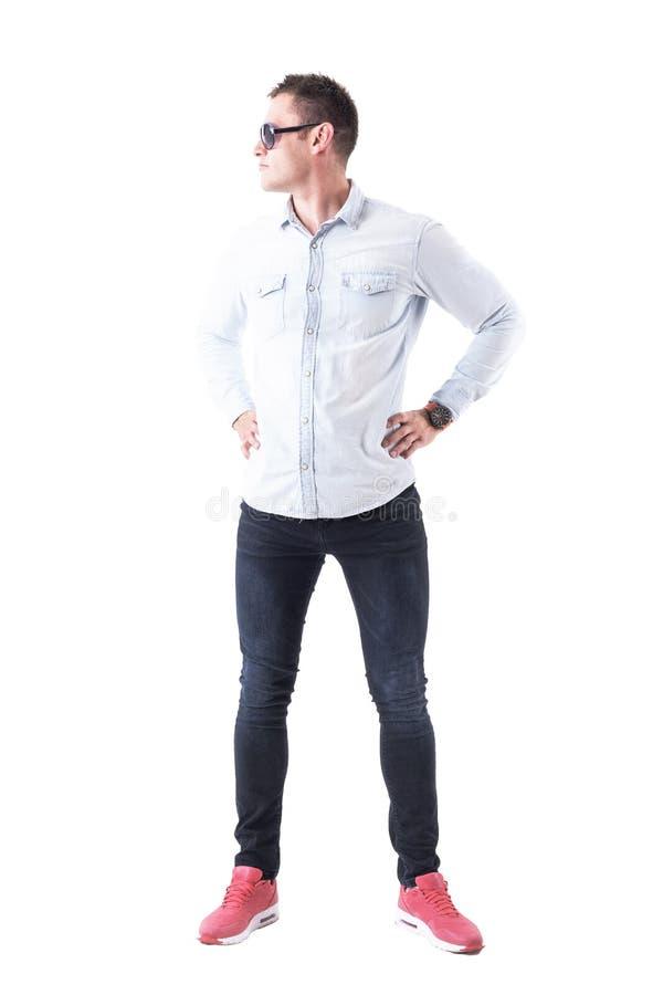 Homem sério seguro da atitude com mãos nos quadris que vestem os óculos de sol que olham afastado imagens de stock royalty free