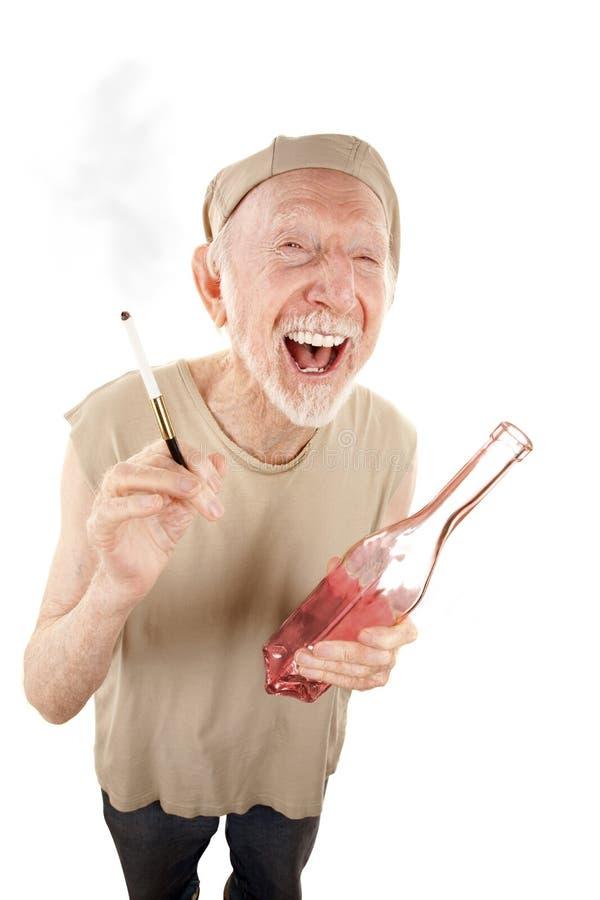 Homem sênior áspero com cigarro e licor fotografia de stock royalty free