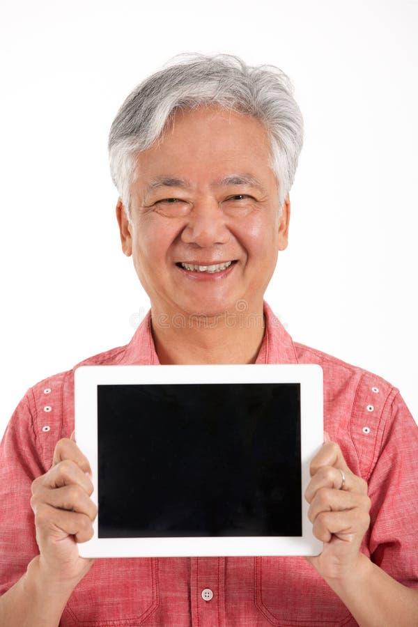 Homem sênior chinês que prende a tabuleta de Digitas fotos de stock