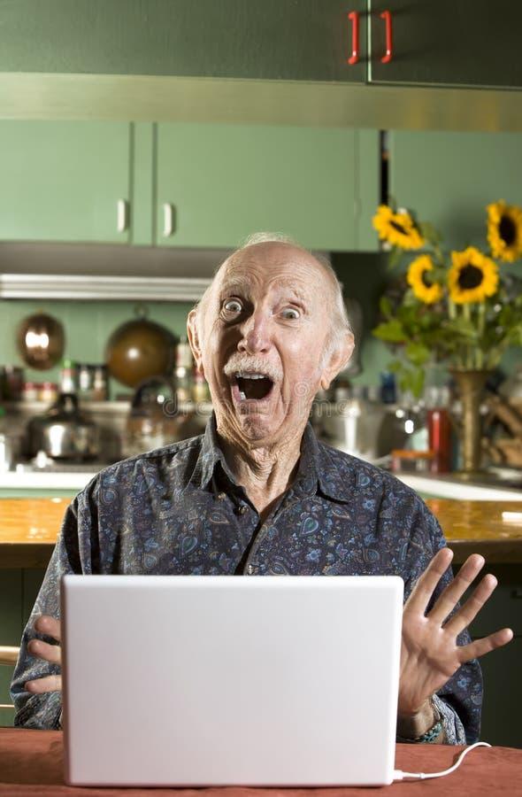 Homem sênior choc com um computador portátil
