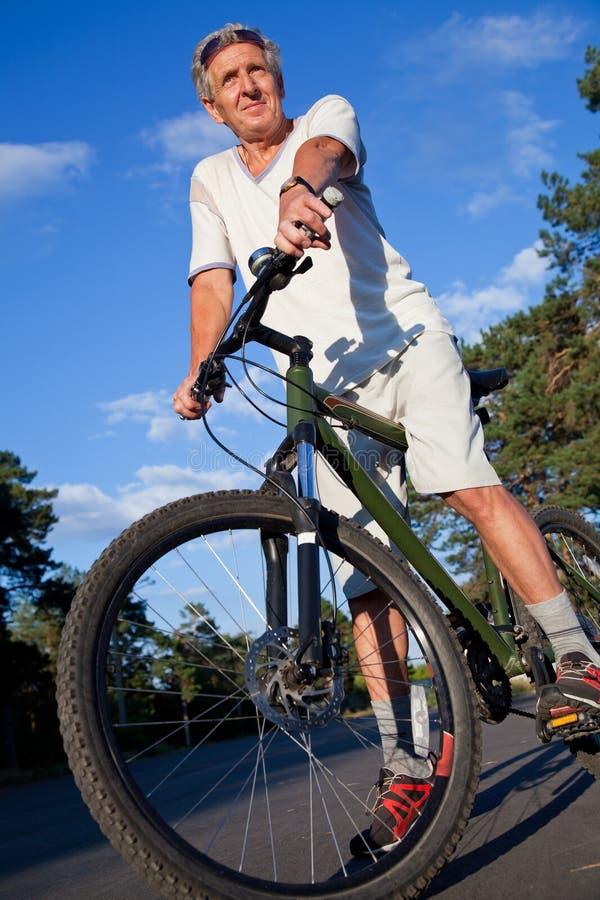 Homem sênior com bicicleta fotografia de stock