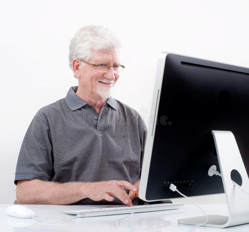 Homem sênior com computador imagem de stock