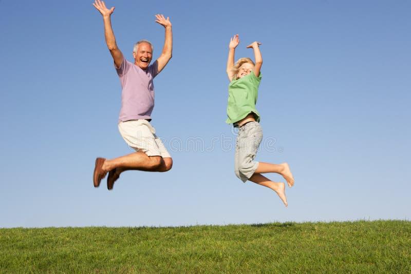 Homem sênior com o neto que salta no ar fotos de stock royalty free