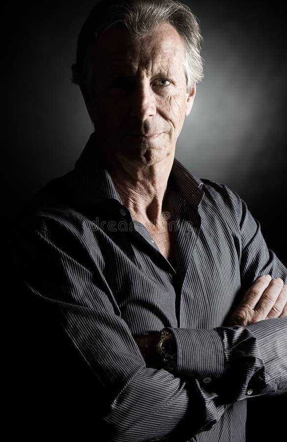 Homem sênior considerável de encontro ao fundo escuro imagem de stock